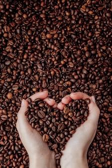 Grãos de café nas palmas das mãos em forma de um coração no fundo do café.
