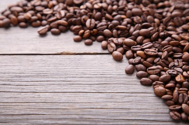 Grãos de café naturais na mesa de madeira cinza