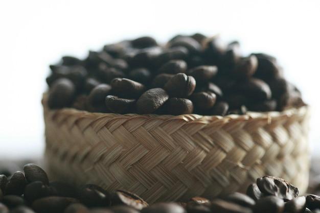 Grãos de café no cesto em fundo de madeira, suave desfoque
