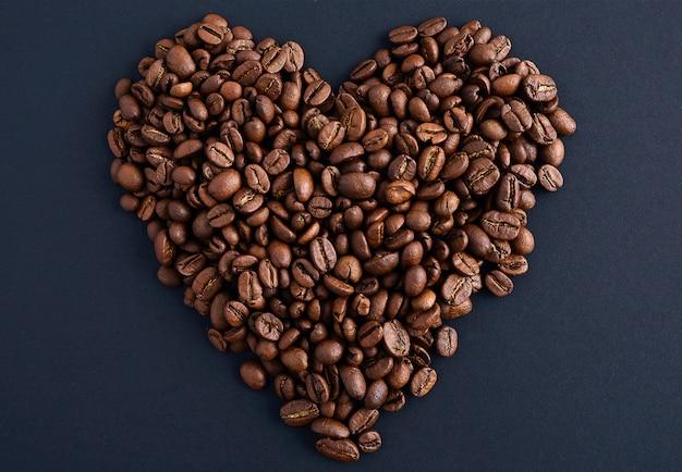 Grãos de café no fundo branco de forma de coração isolado