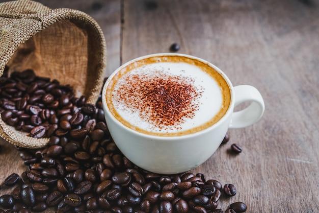 Grãos de café no saco com uma xícara de café no fundo da mesa de madeira.