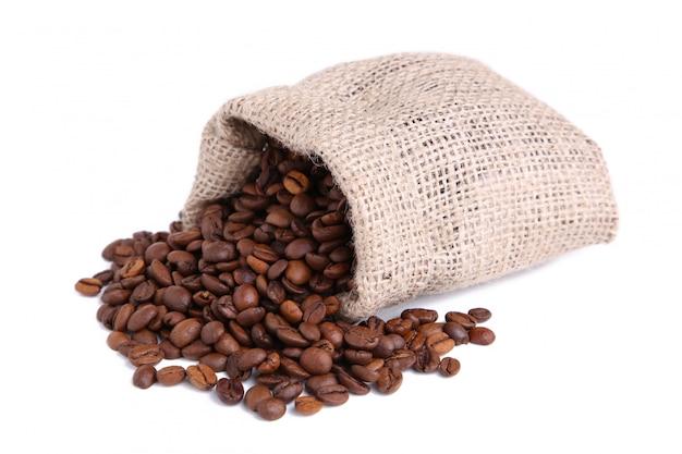 Grãos de café no saco de aniagem isolado no branco