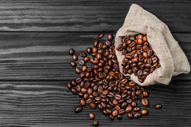 Grãos de café no saco de serapilheira de café na superfície de madeira.