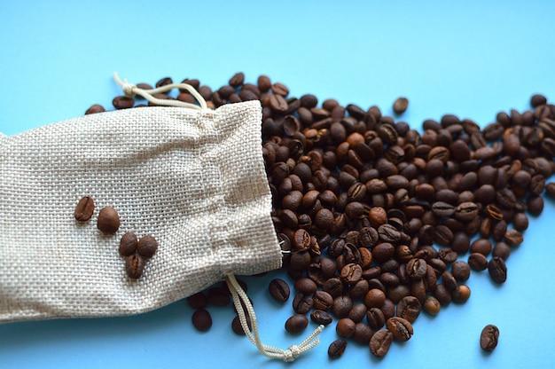 Grãos de café no saco isolado em fundo azul
