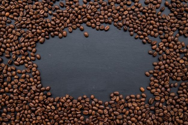 Grãos de café no velho fundo preto da mesa