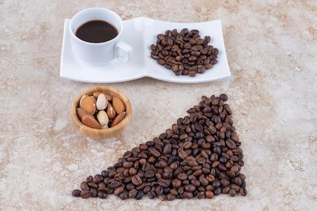 Grãos de café, nozes sortidas e uma xícara de café