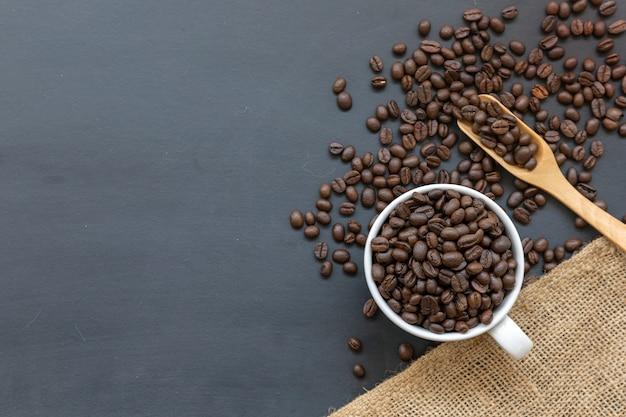 Grãos de café, pano de saco e colher de pau