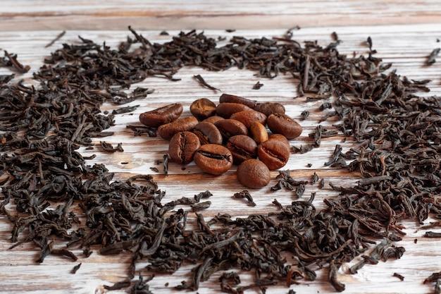 Grãos de café perto de folhas de chá. qual é melhor - chá ou café