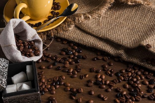 Grãos de café perto de saco, jogo de chá, caixa de açúcar e pano de saco