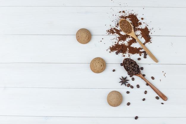 Grãos de café plana leigos na colher de pau com biscoitos, café moído em fundo de madeira. horizontal