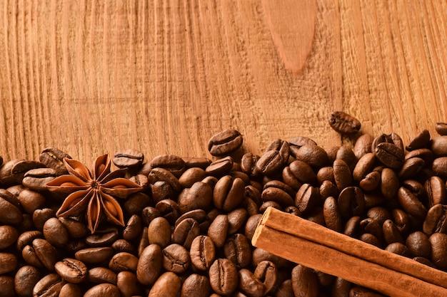 Grãos de café polvilhados na parte inferior da foto, bem como anis e canela.