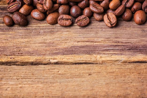Grãos de café preto na mesa de madeira