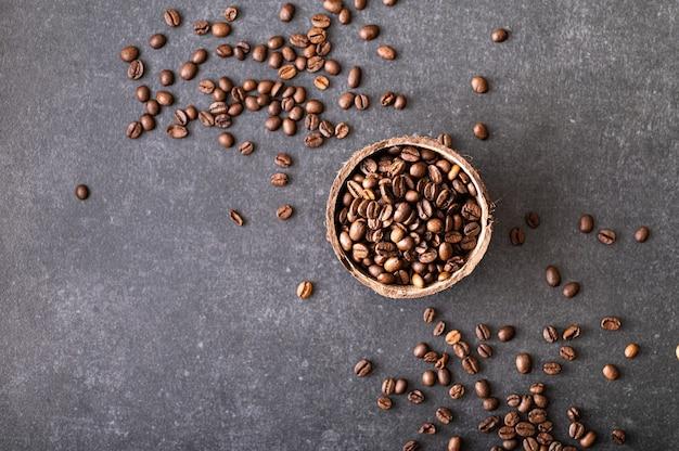 Grãos de café pretos em uma tigela de coco no fundo de concreto
