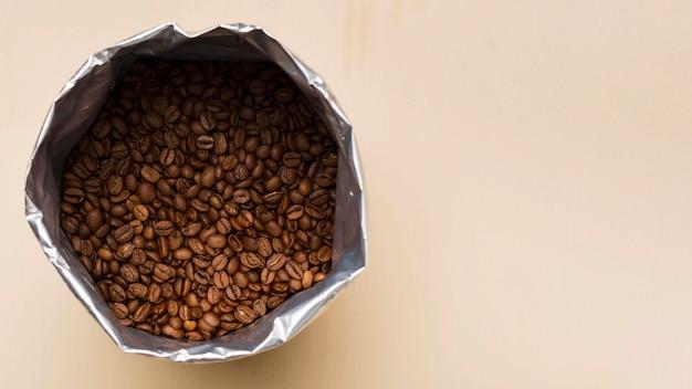 Grãos de café pretos sobre fundo bege com espaço de cópia