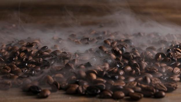 Grãos de café quentes na mesa de madeira