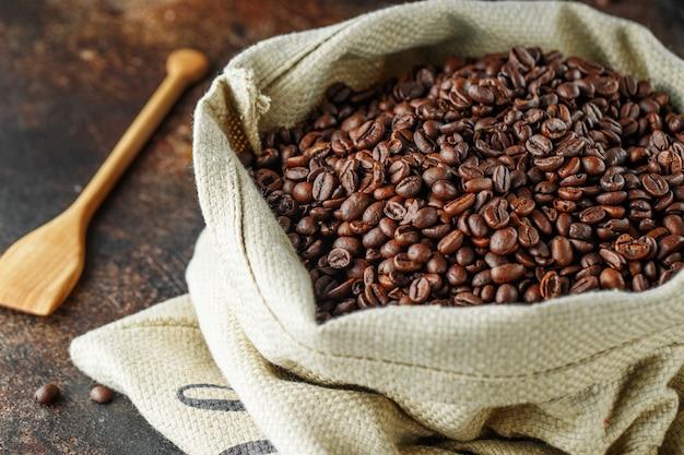 Grãos de café recém-torrados em um saco de estopa