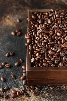 Grãos de café recém torrados em uma caixa de madeira