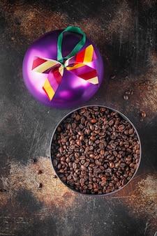 Grãos de café recém-torrados em uma caixa de natal roxa festiva em forma de bola de natal para presente ou presente