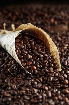 Grãos de café recém-torrados em uma jarra de vidro.