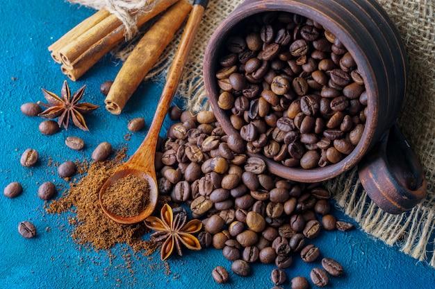 Grãos de café saindo de um copo de barro e espalhados sobre um fundo azul textural