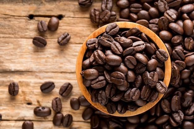 Grãos de café sobre fundo de madeira