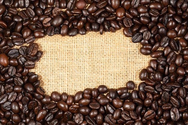 Grãos de café sobre fundo marrom tecido de linho. textura de grãos de café torrado, usado como pano de fundo. vista plana leiga, superior, cópia espaço.