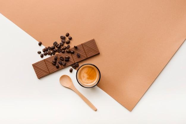 Grãos de café torrados; barra de chocolate e copo de café com colher no fundo