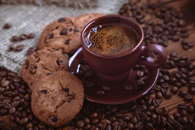Grãos de café torrados, biscoito com chocolate e xícara na superfície de madeira