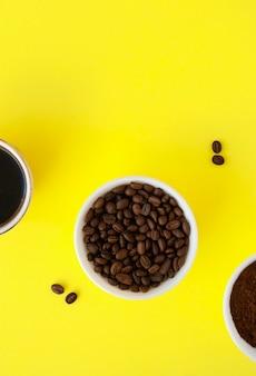 Grãos de café torrados, café moído e café preto moído em tigelas brancas sobre uma superfície amarela.