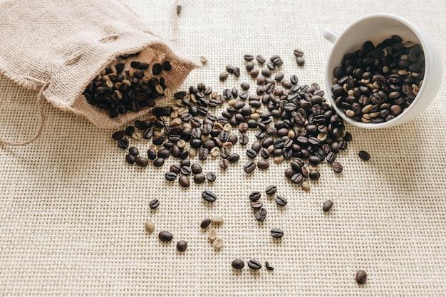 Grãos de café torrados caindo do saco e copo cerâmico