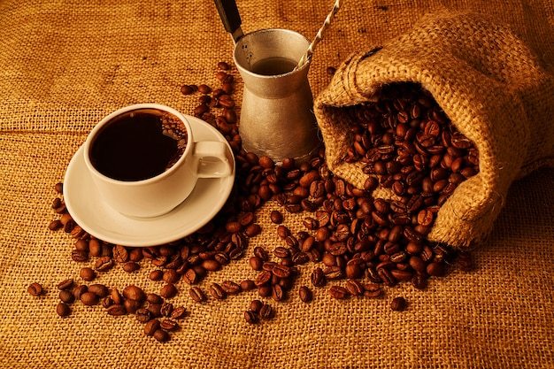 Grãos de café torrados, cezve e xícara de café expresso em pano de saco fundo