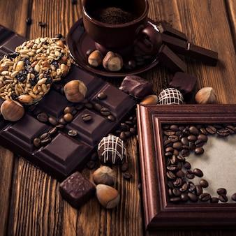 Grãos de café torrados, chocolate, doces, nozes e uma xícara com café moído e a moldura na superfície de madeira.