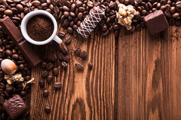 Grãos de café torrados, chocolate, doces, nozes e uma xícara com café moído na superfície de madeira