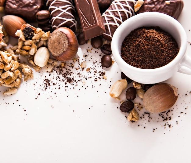 Grãos de café torrados, chocolate, doces, nozes e uma xícara com café moído