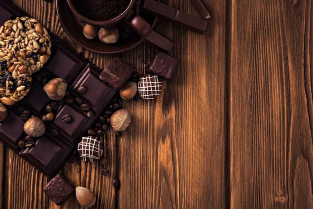 Grãos de café torrados, chocolate, muesli, doces, nozes e xícara na superfície de madeira
