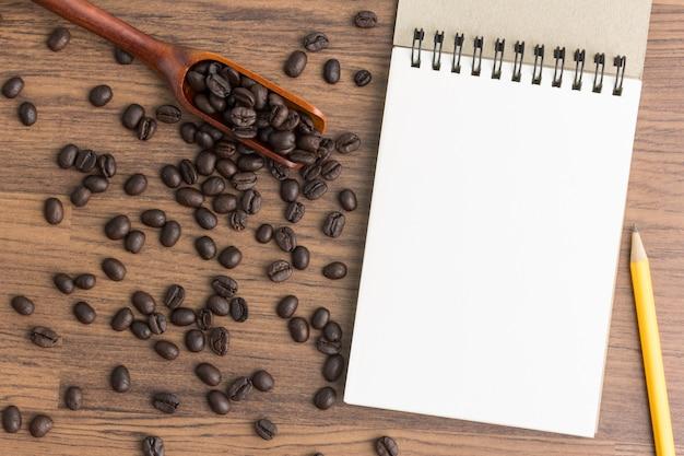 Grãos de café torrados com notebook na vista superior