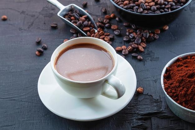 Grãos de café torrados com pó de café e xícaras de café.