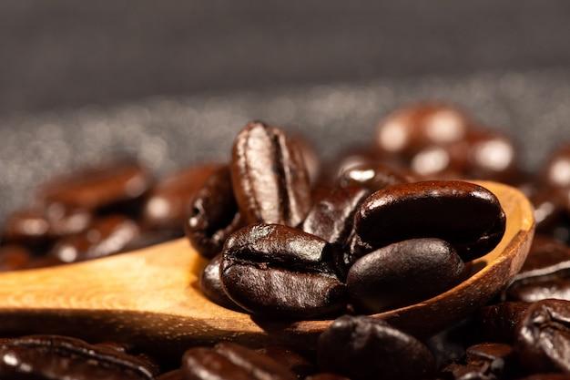 Grãos de café torrados com uma colher de pau
