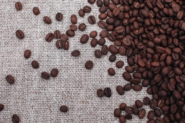 Grãos de café torrados e aromáticos frescos espalhados sobre um fundo bege de estopa