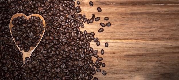 Grãos de café torrados e colher de coração em fundo de madeira