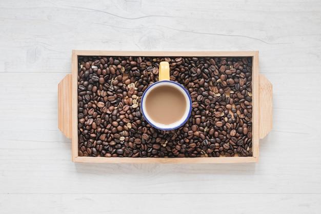 Grãos de café torrados e xícara de café na bandeja de madeira