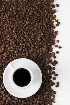 Grãos de café torrados e xícara de café