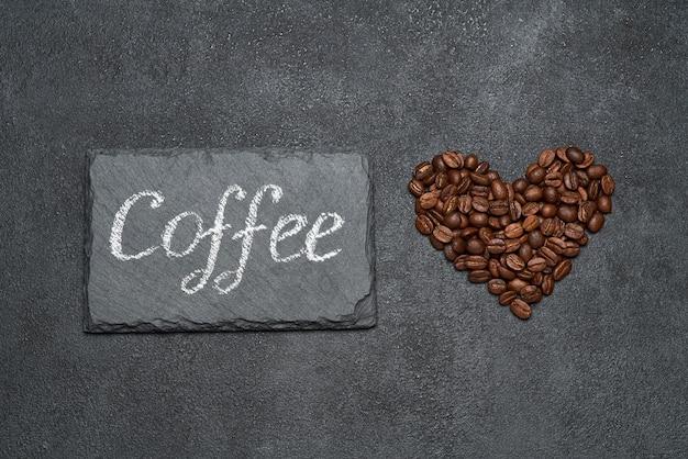 Grãos de café torrados em forma de coração e um sinal escrito à mão na mesa de concreto escuro
