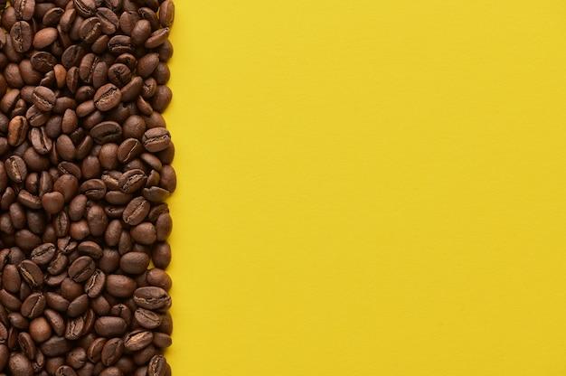 Grãos de café torrados em fundo amarelo com espaço de cópia close-up vista superior