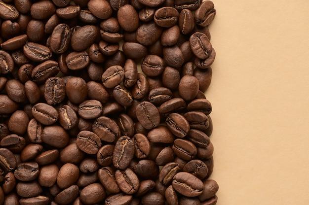 Grãos de café torrados em fundo bege com espaço de cópia. feche a vista de cima.