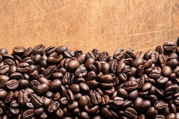 Grãos de café torrados em fundo de madeira velha
