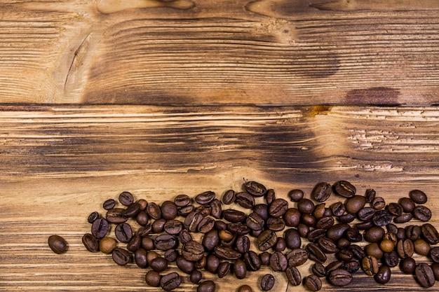 Grãos de café torrados em fundo de madeira