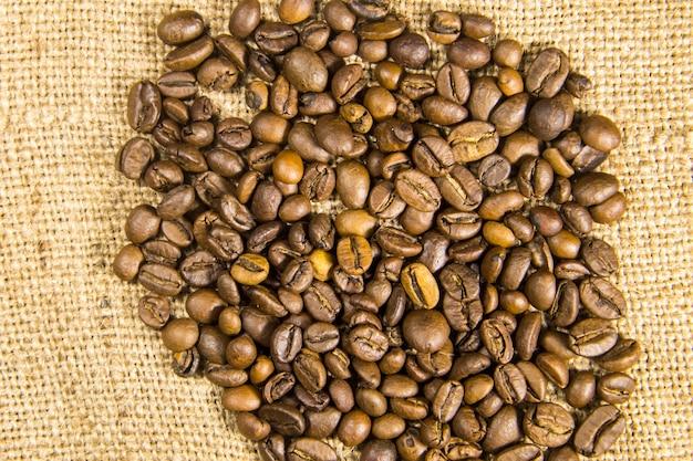Grãos de café torrados em fundo de pano de saco