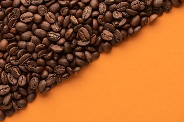 Grãos de café torrados em fundo laranja com espaço de cópia close-up vista superior
