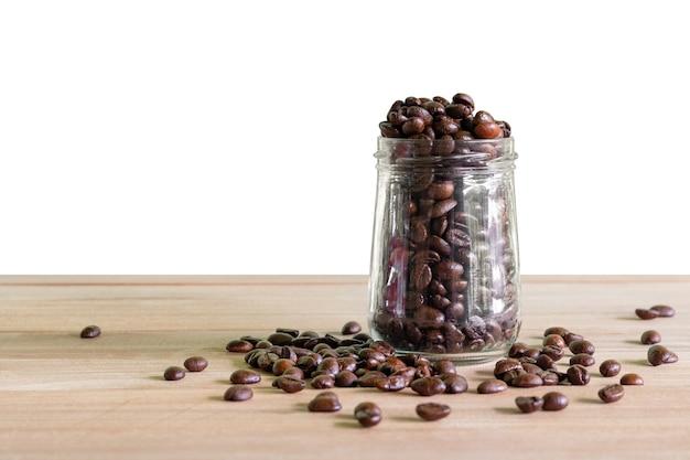 Grãos de café torrados em garrafas de vidro colocadas sobre o fundo da mesa isolado.